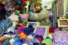 Mężczyzna sprzedawania ciepłe mitynki i skarpety przy Ryskimi bożymi narodzeniami Wprowadzać na rynek Zdjęcie Stock