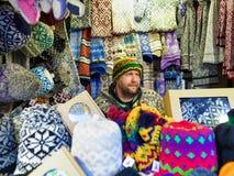Mężczyzna sprzedawanie ciepły odziewa przy Ryskim boże narodzenie rynkiem Obraz Stock