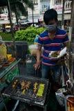 Mężczyzna sprzedawanie piec na grillu jedzenie na Ninh Kieu nocy rynku Obrazy Stock