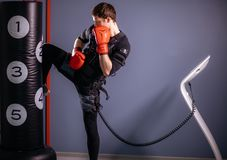 Mężczyzna stażowy kolanowy kopnięcie Kickboxer jest ubranym kostium elektryczny pobudzenie Zdjęcia Royalty Free