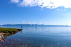 Mężczyzna standind obok Sayram jeziora w niebieskim niebie Zdjęcia Stock