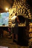 Mężczyzna stawia łupkę w kuchence obrazy stock