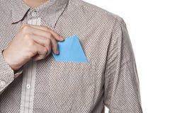 Mężczyzna stawia błękitną kopertę w jego koszulowej kieszeni Obrazy Royalty Free