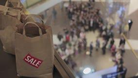 Mężczyzna stawia brown torby z sprzedaż majcherem na mnie na podłoga w centrum handlowym na czarnym Piątku Tłum na tle zbiory