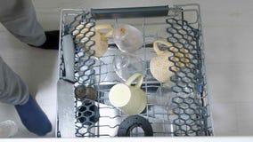 Mężczyzna stawia brudnych naczynia w zmywarka do naczyń zbiory