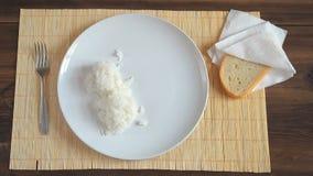 Mężczyzna stawia drewnianą łyżkę na bielu i smażył mięso z warzywami, ceramicznego naczynia warzący parujący ryż zdjęcie wideo
