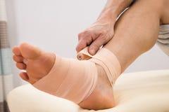 Mężczyzna stawia elastycznego bandaż na stopie obraz stock