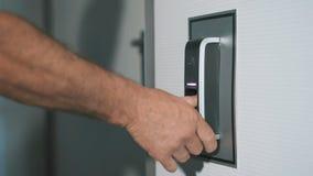 Mężczyzna stawia jego palec na odcisku palca przeszukiwaczu który projektuje wchodzić do drzwi Nowożytna technologia zabezpieczeń zbiory