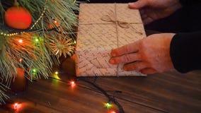 Mężczyzna stawia prezentów pudełka pod choinką Jodła stojak na drewnianym stole i dekorujący z rozjarzoną girlandą i zdjęcie wideo