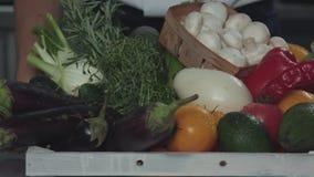 Mężczyzna stawia pudełko warzywa i zielenieje na stole zdjęcie wideo