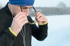 Mężczyzna stawia sportów glasess przed biegać na śniegu Zdjęcie Stock