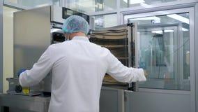 Mężczyzna stawia tubki w chłodziarce w laboratorium zdjęcie wideo