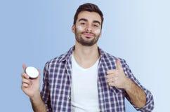 Mężczyzna stawia twarzy śmietankę na policzkach, pokazuje aprobaty Zdjęcie Stock