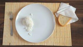 Mężczyzna stawia warzyć, dekatyzujący ryż na białym naczyniu drewniana łyżka zbiory