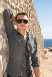 Mężczyzna stoi blisko ściany na sposobie morze w okularach przeciwsłonecznych Zdjęcia Royalty Free