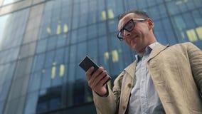 Mężczyzna stoi blisko budynku biurowego i używa smartphone zdjęcie wideo