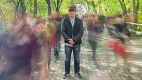 Mężczyzna stoi samotnie w zamazanym tłumu na tło zieleni drzewach, Czasu upływ zbiory wideo