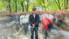 Mężczyzna stoi samotnie w zamazanym tłumu na tło zieleni drzewach, Czasu upływ Kamera rusza się daleko od zdjęcie wideo