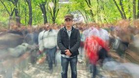 Mężczyzna stoi samotnie w zamazanym tłumu na tło zieleni drzewach, Czasu upływ Kamera zbliża się zbiory