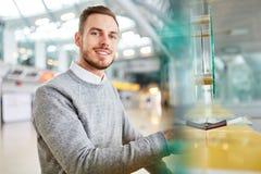Mężczyzna stoi uśmiecha się przy czekiem w biurku fotografia royalty free