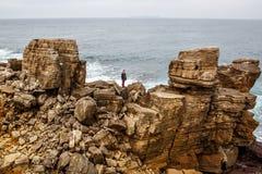 Mężczyzna stojaki na dennej falezie, ciemny burzowy morze na tle Zdjęcia Stock