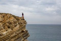 Mężczyzna stojaki na dennej falezie, morze na tle Zdjęcia Stock