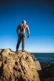 Mężczyzna stojaki na skale morzem przeciw niebu Obrazy Stock