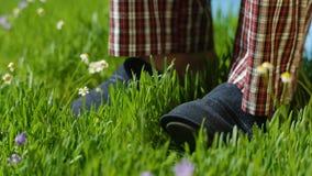 Mężczyzna stojaki na trawie w kapciach Męscy cieki w sneakers na trawie fotografia stock