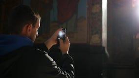 Mężczyzna stojaki w kościół i biorą obrazki na telefonie, łapie skutek obiektyw swobodny ruch 1920x1080 zbiory wideo