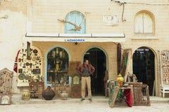 Mężczyzna stojaki wewnątrz przy pamiątkarskiego sklepu wejściem w El Djem, Tunezja Zdjęcia Royalty Free