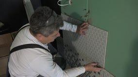 Mężczyzna stosuje ceramiczne płytki łazienki ściana Handheld strza? zdjęcie wideo