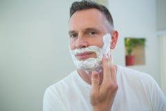 Mężczyzna stosuje golenie pianę na jego twarzy Obrazy Stock
