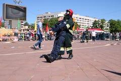 Mężczyzna strażak w fireproof kostiumu i hełma ratunek włóczydeł ciągnieniach maniken przy przeciwogniowymi rywalizacjami, Minsk, obrazy royalty free