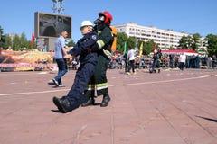 Mężczyzna strażak w fireproof kostiumu i hełma ratunek włóczydeł ciągnieniach maniken rywalizacje, Minsk, Białoruś, 06 06 2018 fotografia royalty free