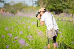 Mężczyzna strzela kwiaty z DSLR outdoors zdjęcie stock