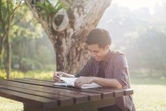 Mężczyzna studiuje samotnie przy parkiem Zdjęcie Royalty Free