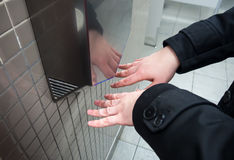 Mężczyzna suszy mokre ręki z ręki elektrycznymi suszarkami obraz stock