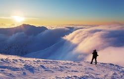 Mężczyzna sylwetka nad chmurami w zimy górze obraz royalty free