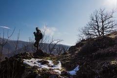Mężczyzna sylwetki pobyt na ostrze skały szczycie Satysfakcjonuje wycieczkowicza cieszy się widok obrazy royalty free