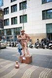 Mężczyzna symuluje rzeźbę kowboj od Amerykańskiego Zachodniego filmu z ubrania malującym brązowym kolorem całkowicie obraz royalty free