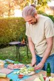 Mężczyzna tnący zucchini na tnącej desce Obraz Royalty Free