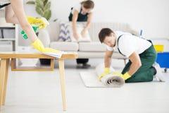 Mężczyzna toczny dywan podczas gdy czyścić zdjęcie stock