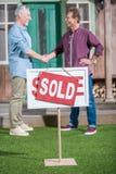 Mężczyzna trząść ręki z saleman i kupuje dom Zdjęcia Stock