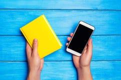 Mężczyzna trzyma żółtą książkę i telefon na błękitnym drewnianym tle Wybór między nauką i telefonem Telefoniczny nałóg obrazy royalty free