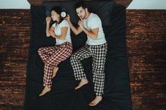 Mężczyzna Trzyma budzika blisko kobieta ucho na łóżku fotografia royalty free