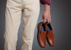 Mężczyzna trzyma buty w ręce fotografia stock