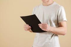 Mężczyzna trzyma czarnego A4 papier Czyta broszurę Ulotki prezentacja Zdjęcie Stock