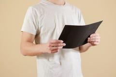 Mężczyzna trzyma czarnego A4 papier Czyta broszurę Ulotki prezentacja Zdjęcia Royalty Free