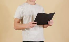 Mężczyzna trzyma czarnego A4 papier Czyta broszurę Ulotki prezentacja Obraz Stock
