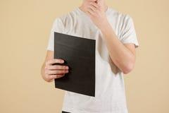 Mężczyzna trzyma czarnego A4 papier Czyta broszurę Ulotki prezentacja Obraz Royalty Free